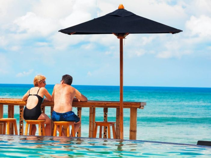 retired couple on beach enjoying early retirement