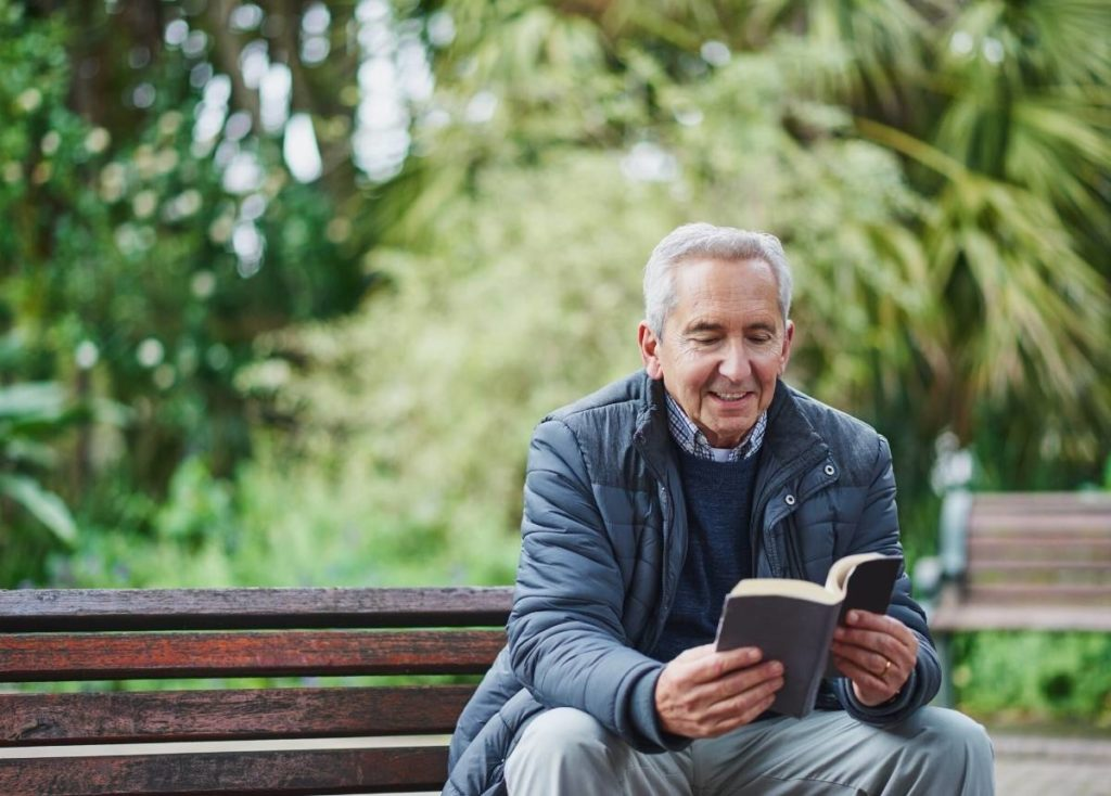 A senior man reading a book in the park