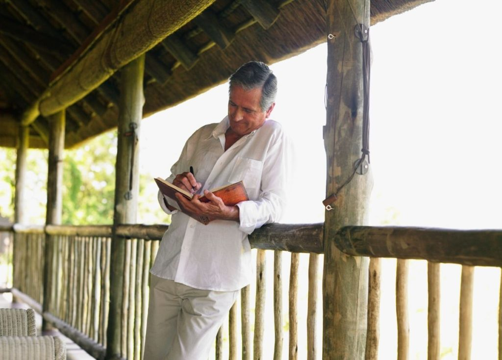 Senior male journaling on porch