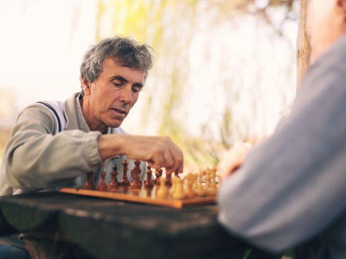 Senior men playing chess as hobby in park