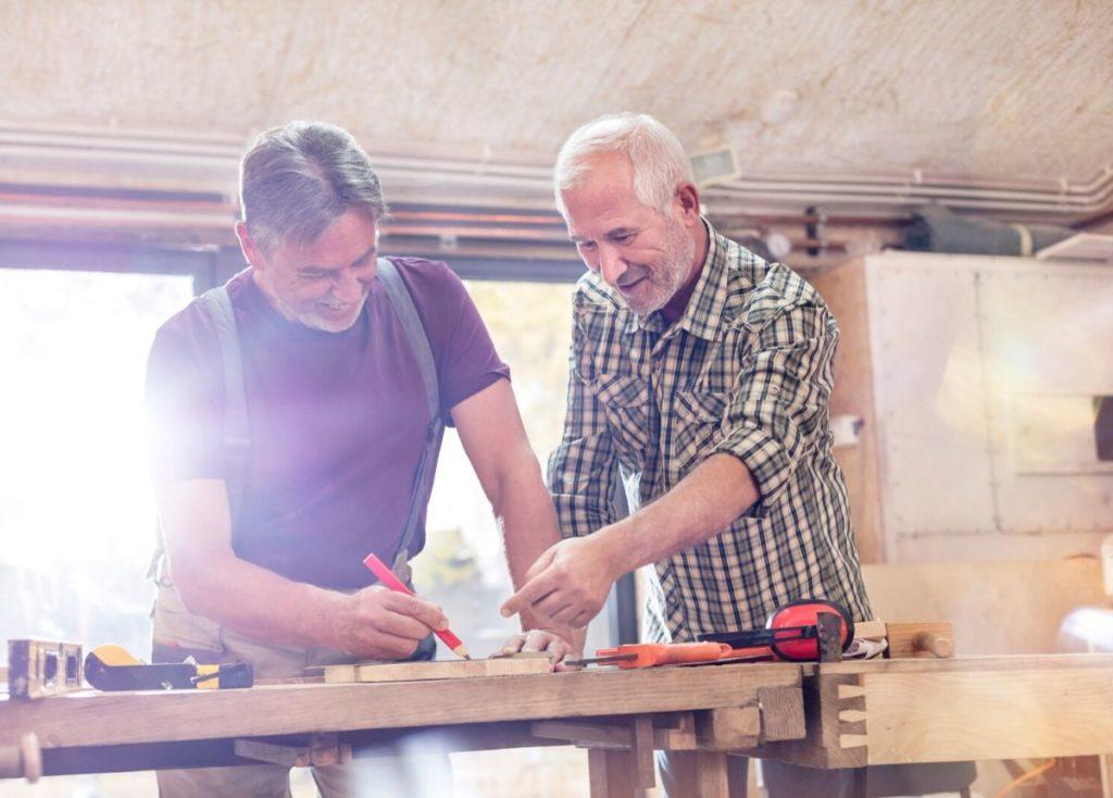 retired men woodworking together